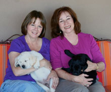 two friends holding their newest bestest new friends -- one a happy yellow lab puppy, the other a joyful black lab puppy